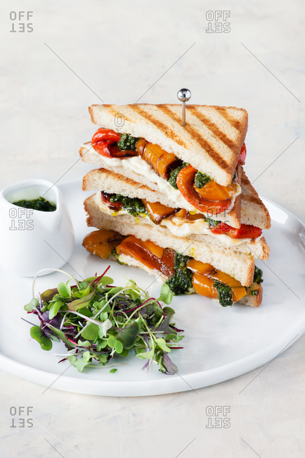 Sandwich with cheese, grilled pepper and pesto on white plate, served with greens