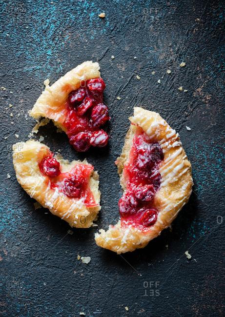 Cherry mini Danish pastry over dark backdrop, top view