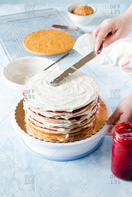 Putting frosting on Russian honey layered cake (Medovik)