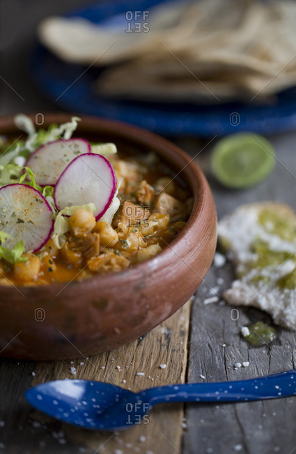 Mexican pozole soup with peltre spoon and pottery dish