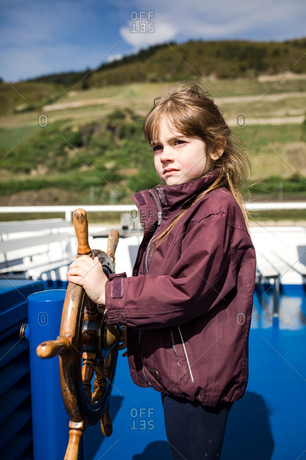 Young girl steering a boat steering wheel