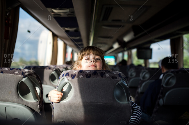 Little girl looking over the back of a bus seat
