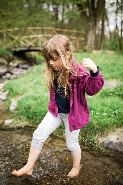 Young girl walking barefoot in a creek