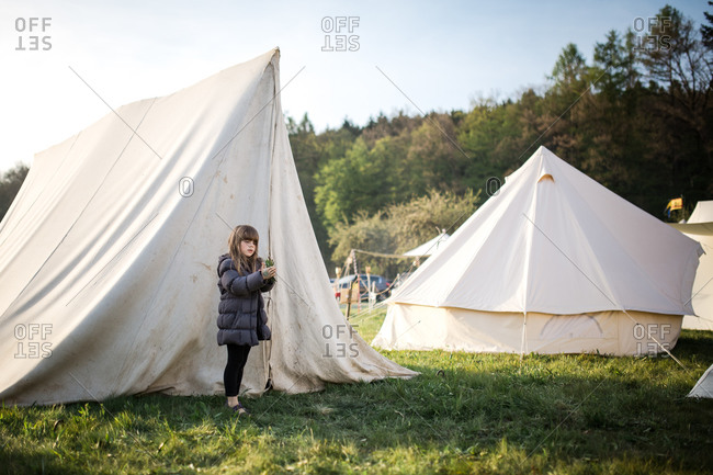 Little girl standing outside of a tent