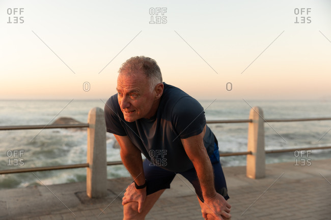 Jogger stretching on seaside