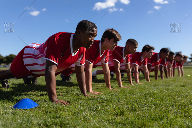 Rugby team doing push-ups on the playing field