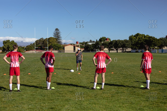 Coach talking and giving instructions to rugby players