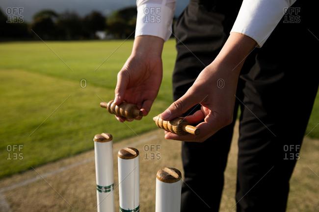Cricket umpire preparing the stumps