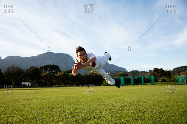 Cricket player trying to catch a cricket ball on the pitch