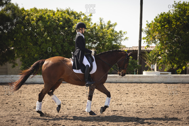 Caucasian woman riding her dressage horse