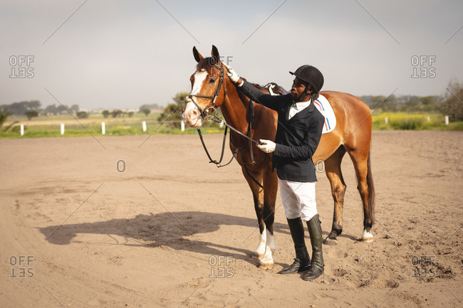 Man caressing his horse before dressage horse jumping event