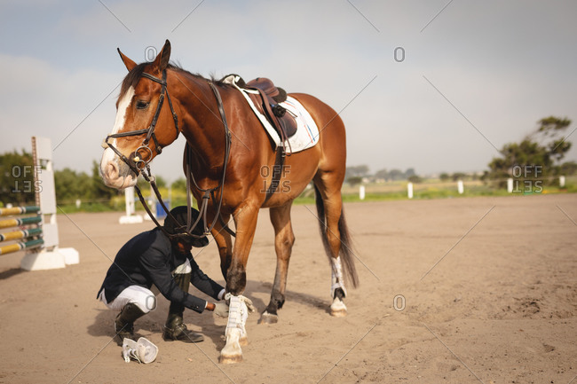 Man preparing his horse before dressage horse jumping event