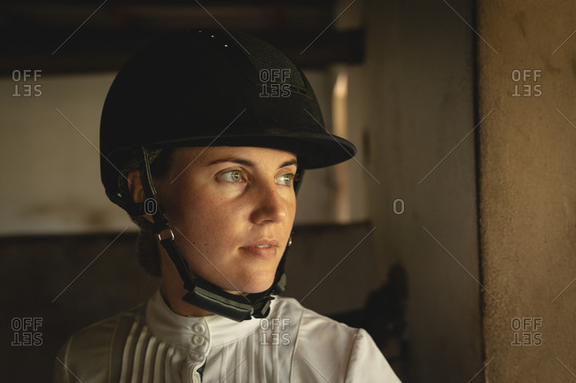 Caucasian woman with helmet standing inside a dressage horse stable