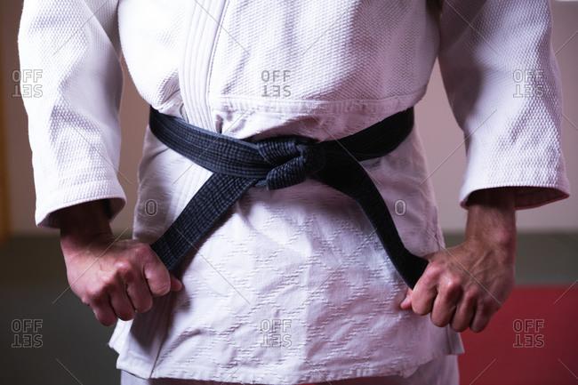 Judoka putting on the black belt