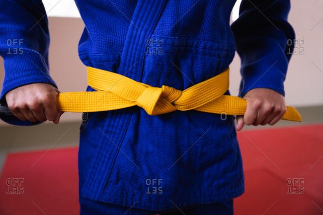 Judoka putting on the yellow belt