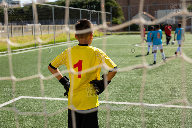 Soccer match seen from behind the goal