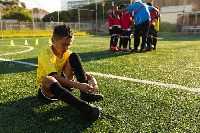 Front view soccer player putting on his shoes