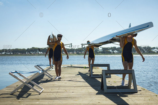 Teammates carrying two rowing boats