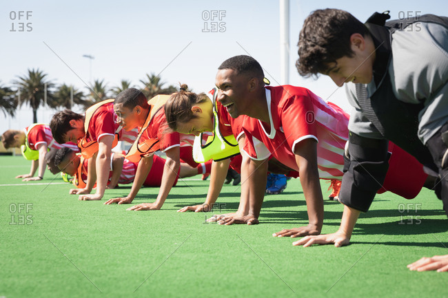 Field hockey players doing push ups on a field