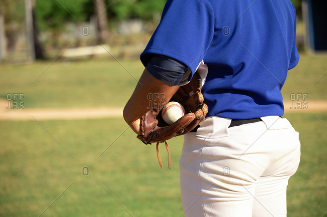 Baseball player holding the ball with baseball gloves
