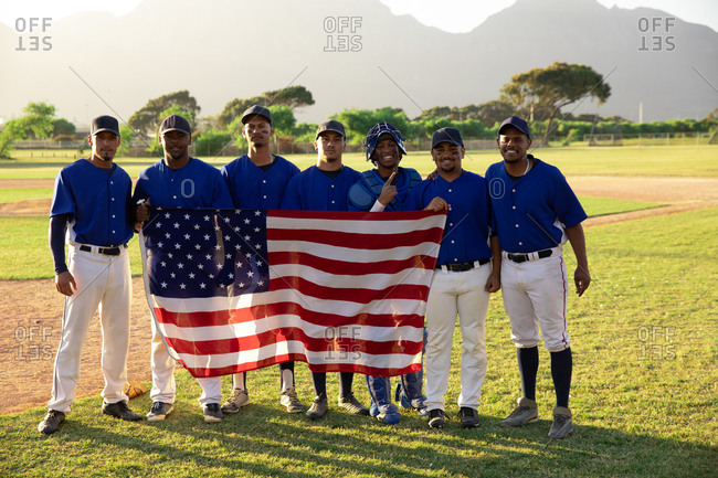 Baseball players standing on line with an american flag