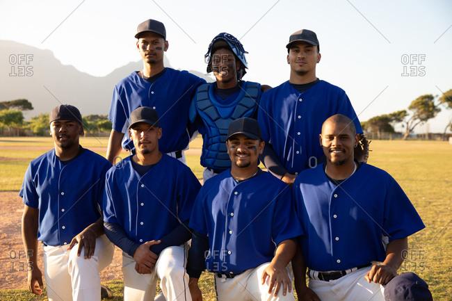 Baseball players standing on line and  kneeling
