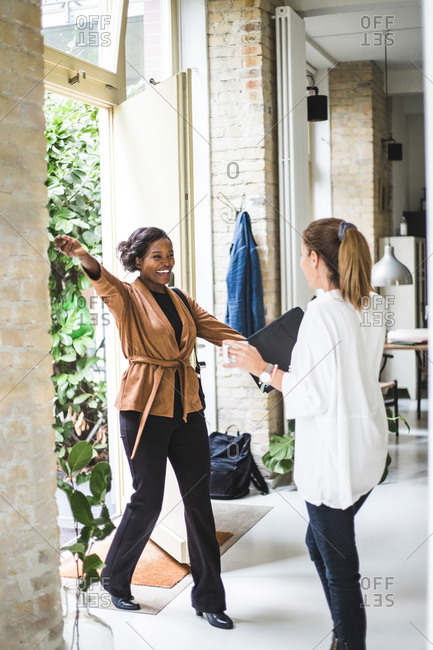Happy female architect greeting coworker while entering in house