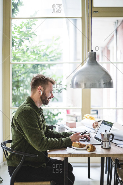 Smiling entrepreneur using laptop while sitting and working at home