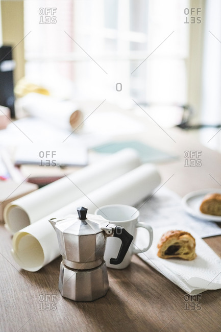 High angle view of teapot with documents rolled up on table