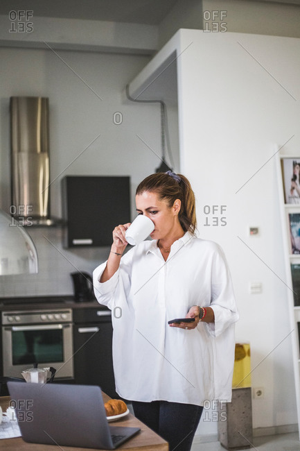 Female entrepreneur drinking while standing and looking at laptop at home