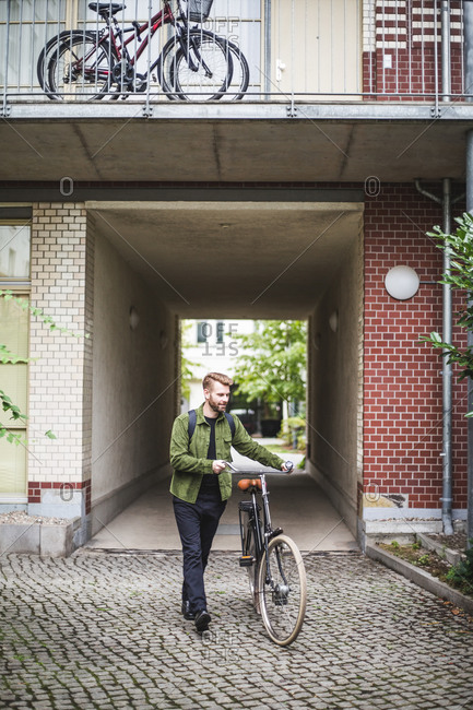 Male architect with bicycle walking on footpath