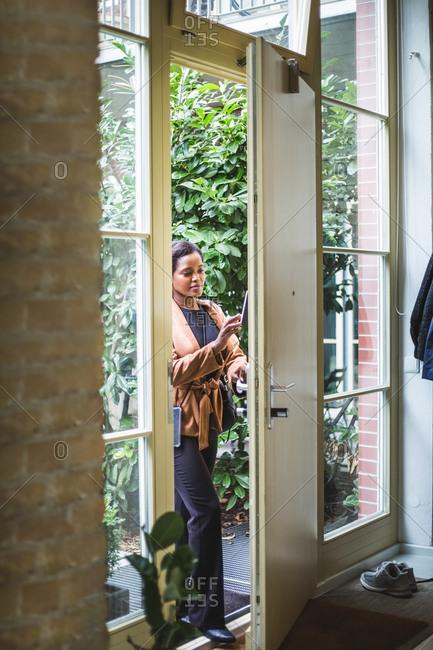 Female entrepreneur unlocking and entering in home