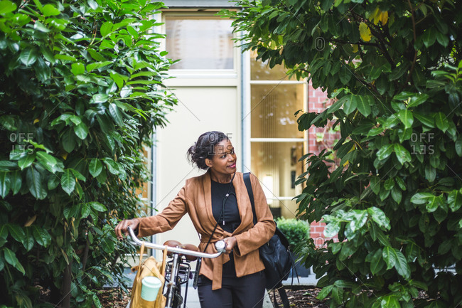 Smiling female architect looking away while standing with bicycle against house