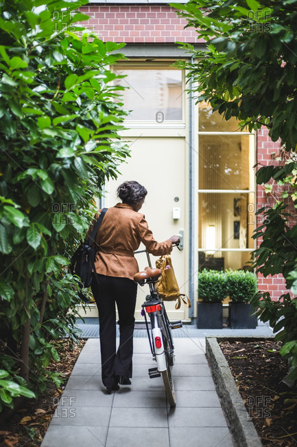 Rear view of female architect with bicycle standing against house