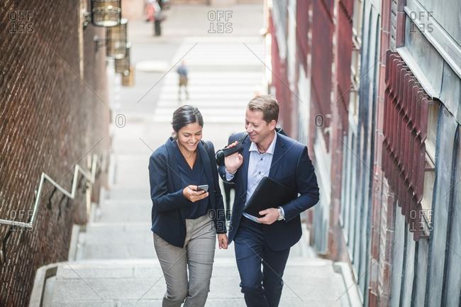 Smiling male and female entrepreneurs using phone while climbing staircase in city