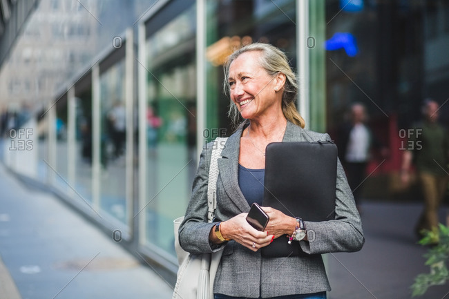 Happy mature businesswoman looking away while standing against office building