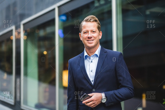 Portrait of smiling mature businessman with smart phone standing against office building