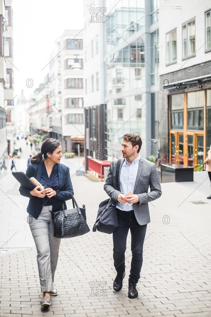 Male and female business professional talking while walking in city