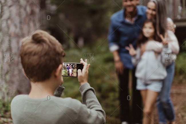 Boy taking picture of family with mobile phone while standing in backyard