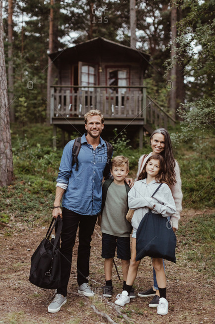 Full length portrait of family with luggage standing against house in forest