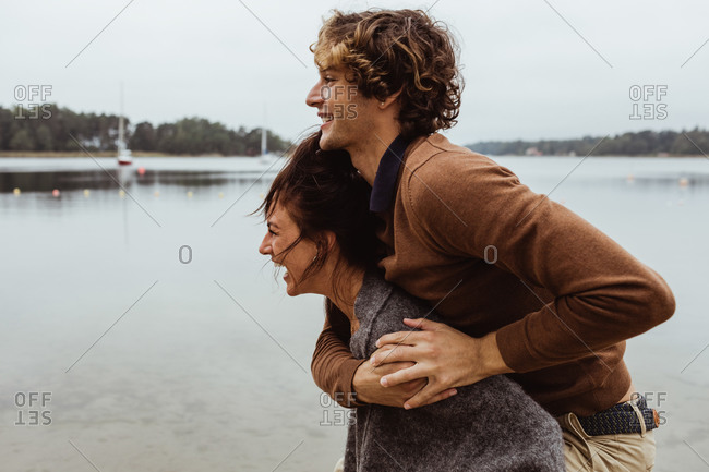 Smiling woman giving piggyback ride to male friend by sea against sky