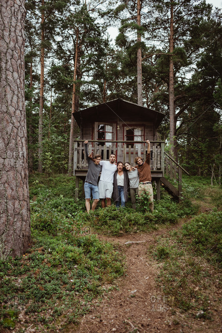 Cheerful friends with arms around standing against house in forest during vacation