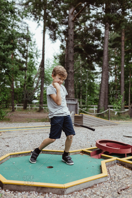 Full length of cheerful boy playing miniature golf in backyard during vacation