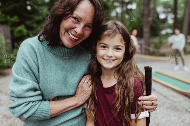 Portrait of smiling grandmother with granddaughter standing outdoors