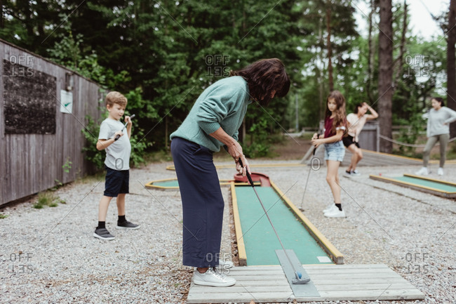 Full length of woman playing miniature golf with family in backyard