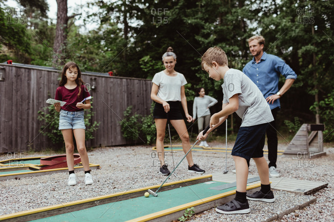 Full length of family looking at boy playing miniature golf in backyard