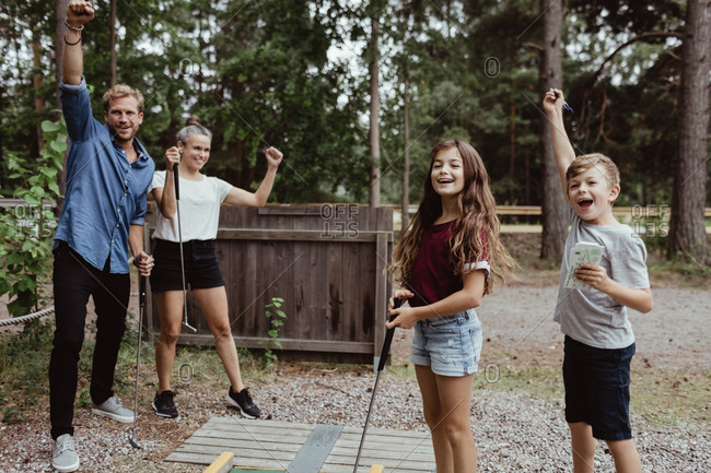 Cheerful family with arms raised playing miniature golf in backyard