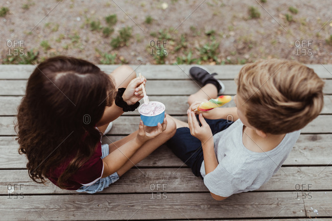 High angle view of siblings eating sweet food while sitting on wooden steps