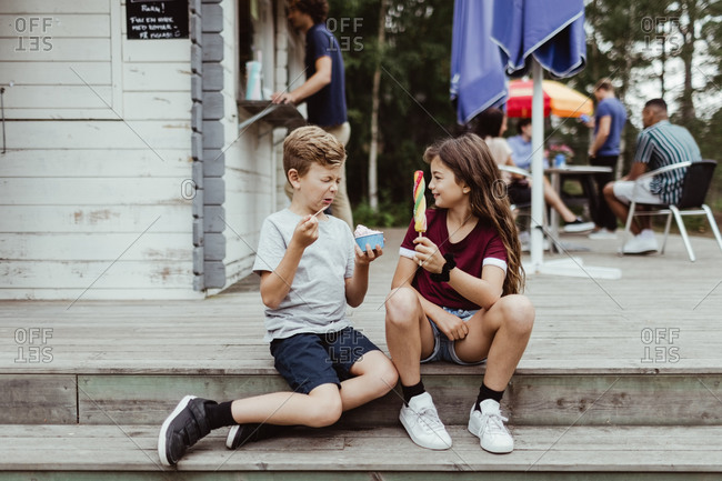 Full length of brother and sister eating sweet food while sitting on wooden steps