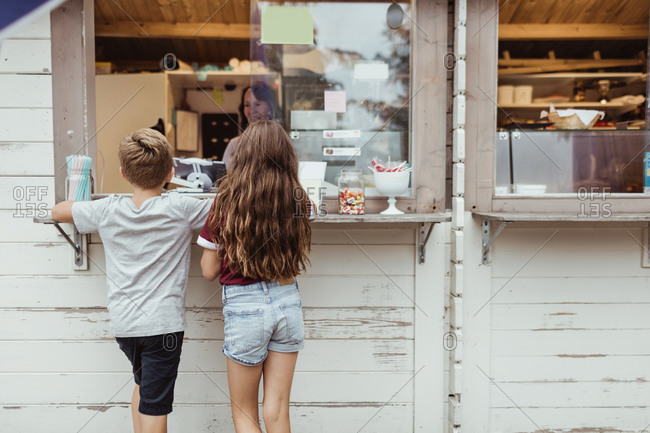 Rear view of siblings standing by concession stand during vacation